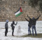 JERUSALEM, ISRAEL - DECEMBER 12:  Palestinian play and wave the Palestinian flag in the snow near the Damascus gate on December 12, 2013 outside Jerusalem's old city, Israel. A heavy winter storm hit much of the Middle East yesterday evening into today, forcing the closure of roads and schools while covering widespread areas with snow and ice.    (Photo by Uriel Sinai/Getty Images) ORG XMIT: 456607021